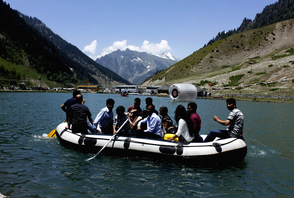 Tourists enjoy themselves aboard a raft on a spectacular blue water lake in Sonamarg - a hill station located in Ganderbal district of Jammu and Kashmir on July 6, 2014. (Photo: IANS)