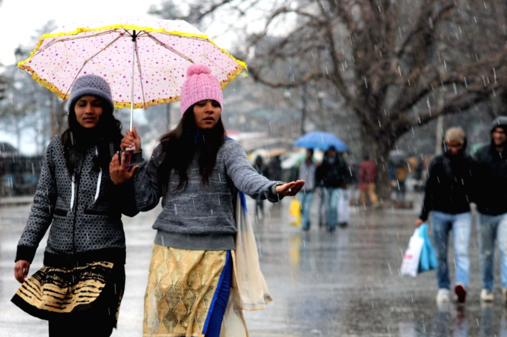 Tourists enjoy themselves after snowfall in Shimla on Feb 13, 2018.