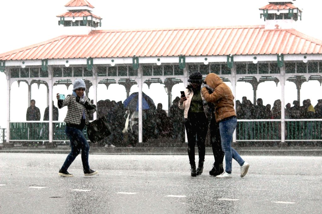 Tourists enjoy themselves during rains, in Shimla on Feb 7, 2019.