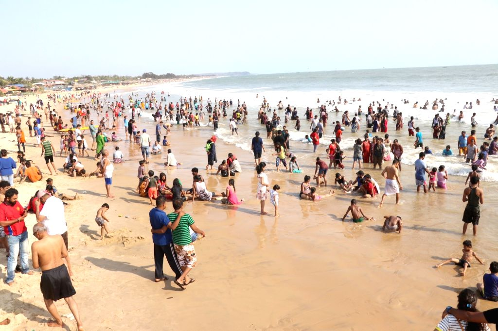 Tourists enjoy themselves on Baga beach in Goa on May 11, 2019.