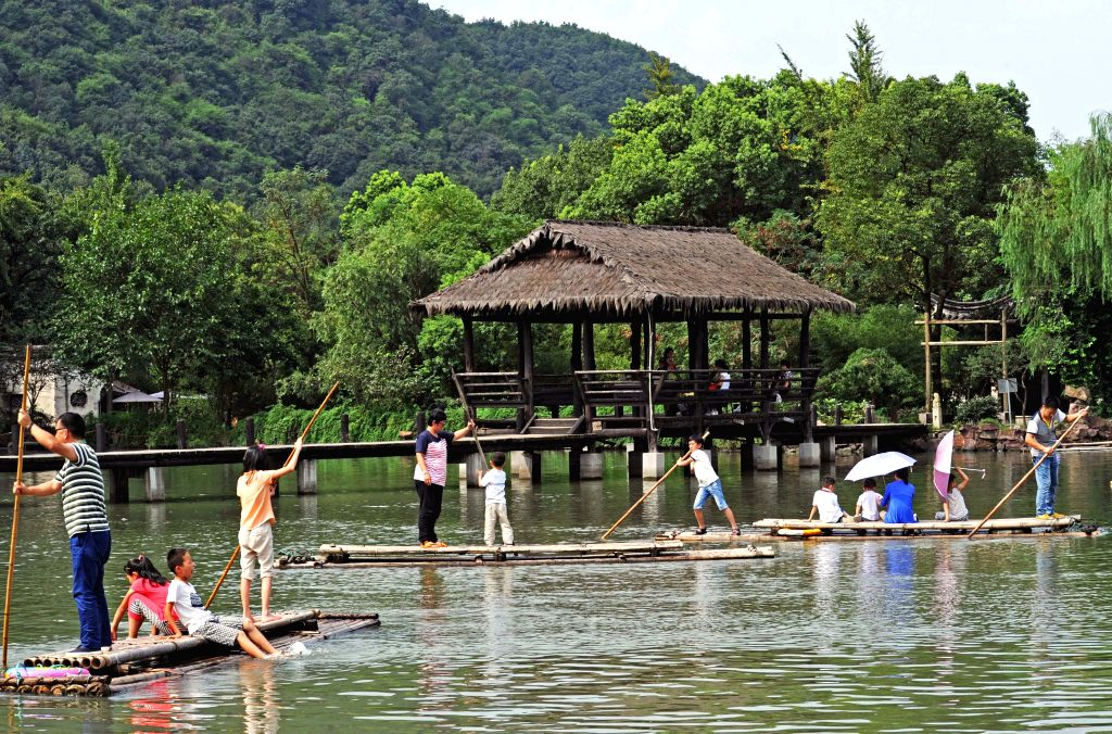 Tourists have fun with bamboo rafting at the Lanting scenic area in Shaoxing, east China's Zhejiang Province, August 25, 2015. According to the latest figures ...