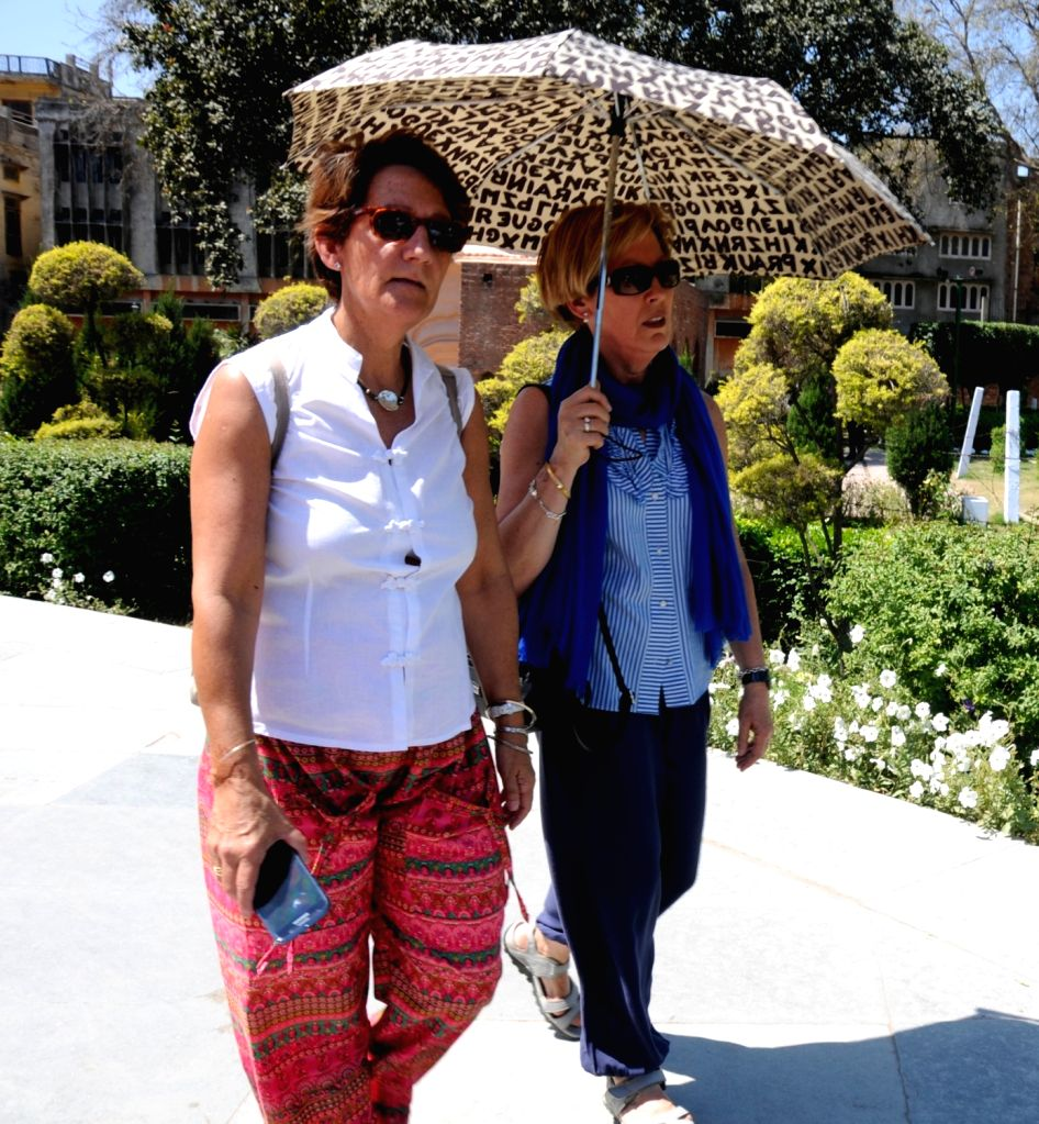 Tourists use umbrella to shield from scorching heat at Jallianwala Bagh on a hot day in Amritsar, on April 12, 2016.