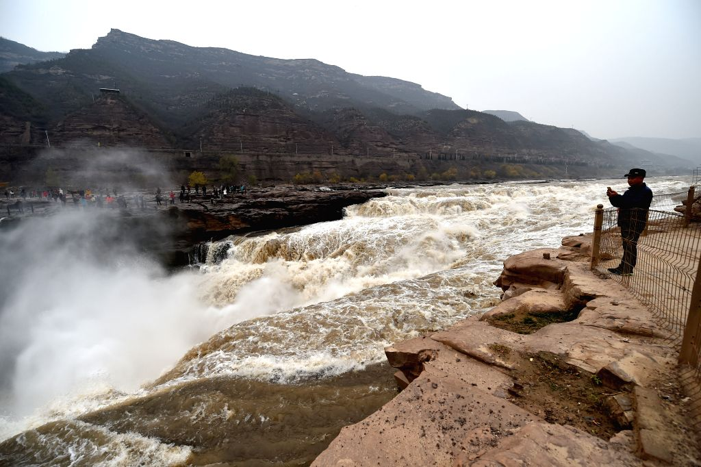 Tourists visit the Hukou Watterfall of the Yellow River in Jixian County, north China's Shanxi Province, Nov. 16, 2015. Rainfall upstream created the magnificent ...