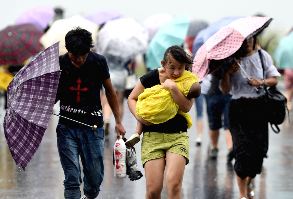 Tourists walk in rain on the Duanqiao bridge in the West Lake scenic spot in Hangzhou, capital of east China's Zhejiang  Province, Aug. 8, 2015. Rainstorms and ...