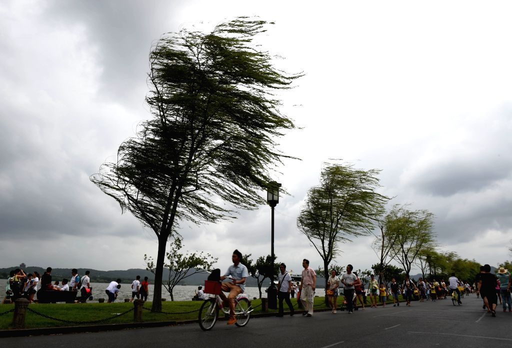 Tourists walk on the Bai causeway in the West Lake scenic spot in Hangzhou, capital of east China's Zhejiang  Province, Aug. 8, 2015. Rainstorms and gales brought ...