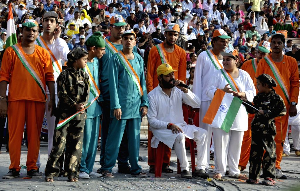 Tourists wave Indian flag during the daily beating of the retreat ceremony at the India-Pakistan Wagah border post near Amritsar on Aug. 15, 2017.