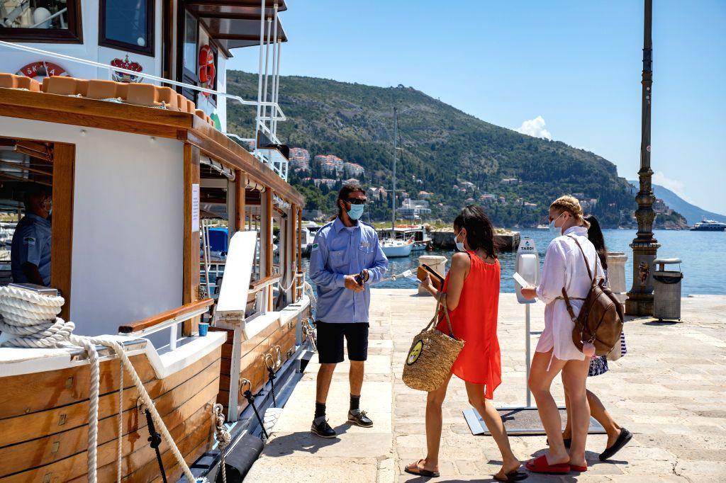 Tourists wearing face masks board a boat in Dubrovnik, Croatia, on June 25, 2020.