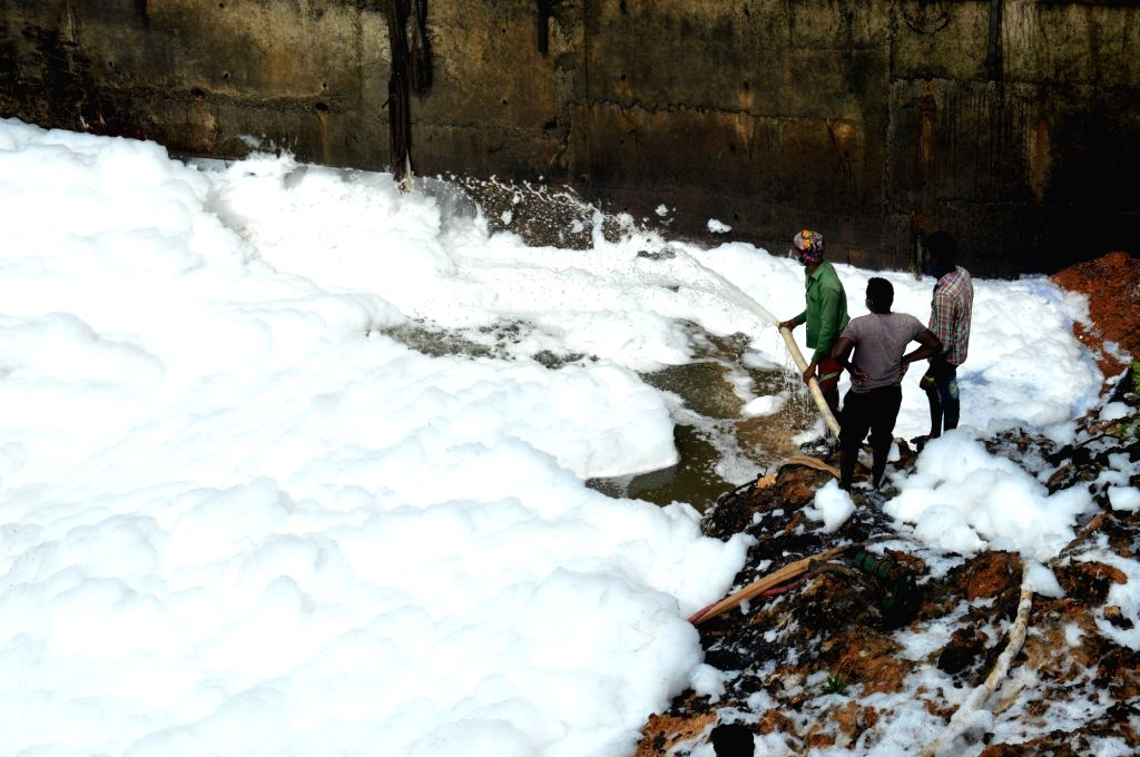 Toxic foam spills over a road from the Bellandur Lake in Bengaluru on Aug 17, 2017.