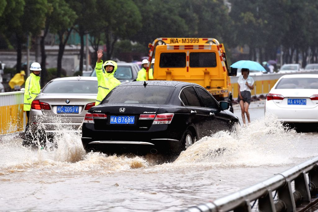 Traffic police direct cars to pass the flooded street in Fuzhou, southeast China's Fujian Province, Aug. 9, 2015. Typhoon Soudelor stormed through Fujian after it ...