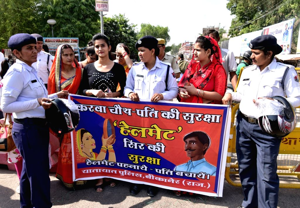 Traffic police personnel during an awareness campaign regarding the usage of helmets ahead of 'Karwa Chauth' - a day long fast observed by married Hindu women (from sunrise to moon rise) for ...