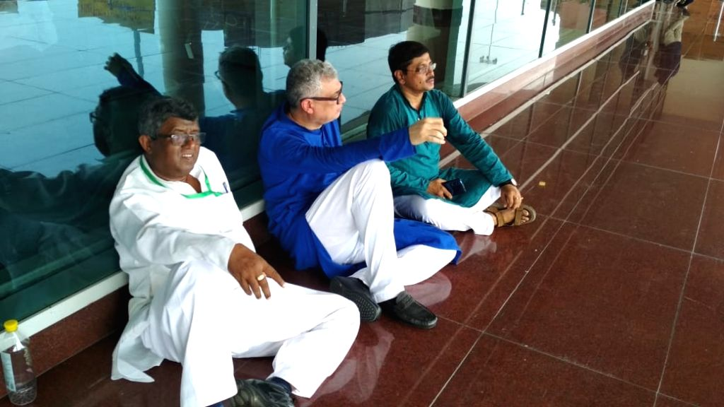 Trinamool Congress leaders Derek O'Brien, Sunil Mondal and Abhir Ranjan Biswas stage a dharna at Varanasi airport after they were stopped from visiting Sonebhadra district in Uttar Pradesh, where 10 ...