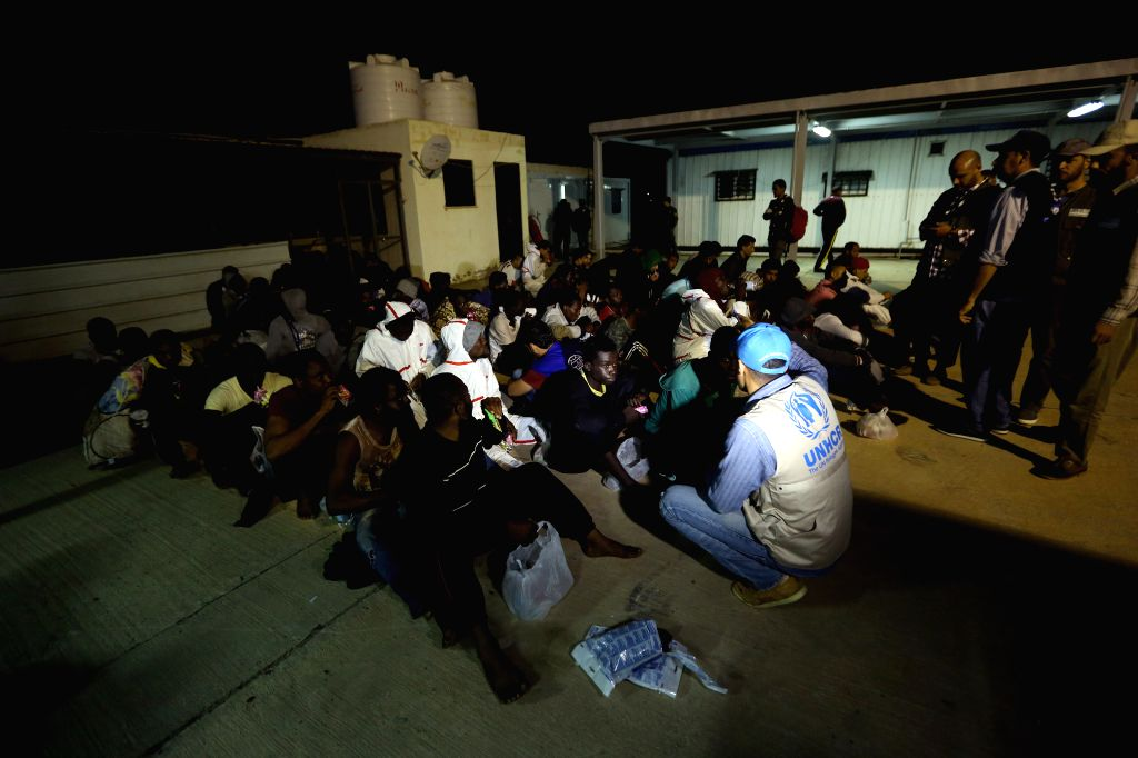 TRIPOLI, April 1, 2018 - Rescued illegal migrants sit on the ground at a naval base in Tripoli, Libya, on March 31, 2018. The Libyan navy on Saturday rescued 125 illegal migrants en route to Europe ...