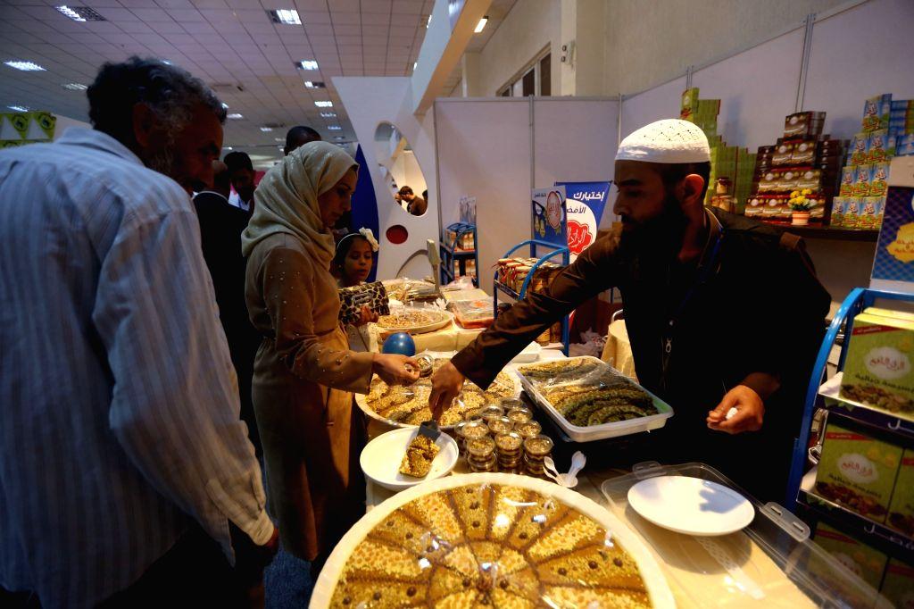 TRIPOLI, April 3, 2018 - An exhibitor sells food on the 46th Libyan Tripoli International Fair in Tripoli, Libya, on April 2, 2018. The 46th Libyan Tripoli International Fair kicked off on Monday ...