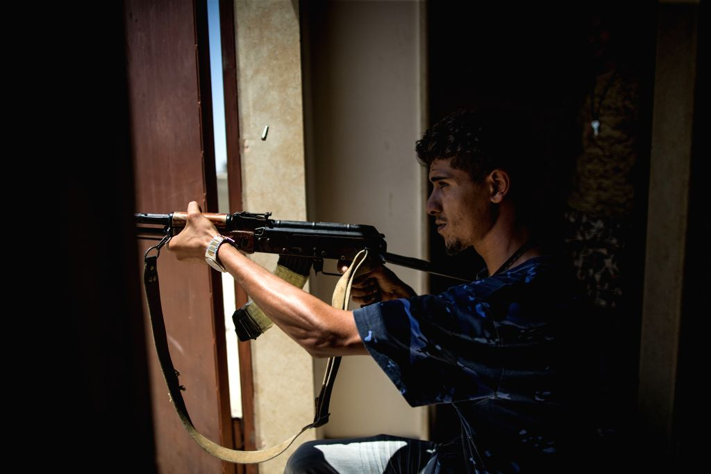 TRIPOLI, Aug. 13, 2019 - A fighter of the UN-backed Government of National Accord (GNA) fires during clashes with the east-based Libyan National Army (LNA) at a frontline in Tripoli, Libya, on Aug. ...