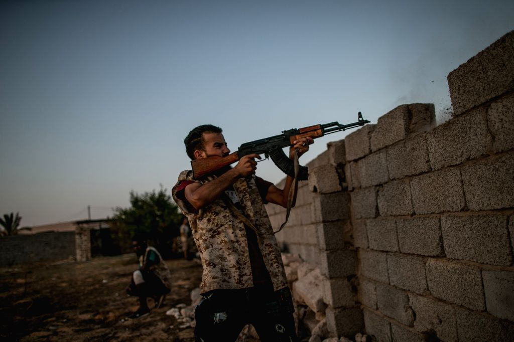 TRIPOLI, Aug. 25, 2019 - A fighter of Libya's UN-backed Government of National Accord (GNA) fires during clashes with forces of the east-based Libyan National Army (LNA), at the Al-Yarmook frontline, ...