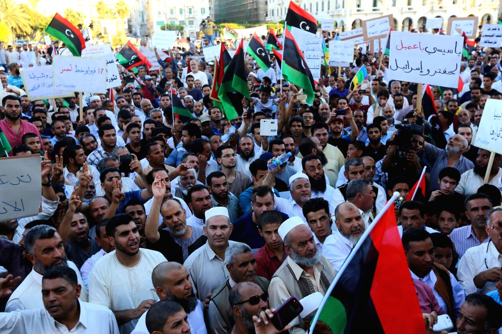 Demonstrators chant slogans and wave national flags on the Martyrs Square in Tripoli, Libya, on Aug. 29, 2014. Hundreds of Tripoli citizens took to the street on ...
