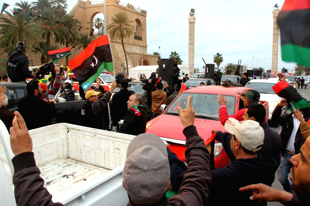 Tripoli's policemen and troops drive their armed vehicles passing Martyrs Square in Tripoli, Libya, on Feb. 16, 2015. Police and army forces paraded on Monday in ...