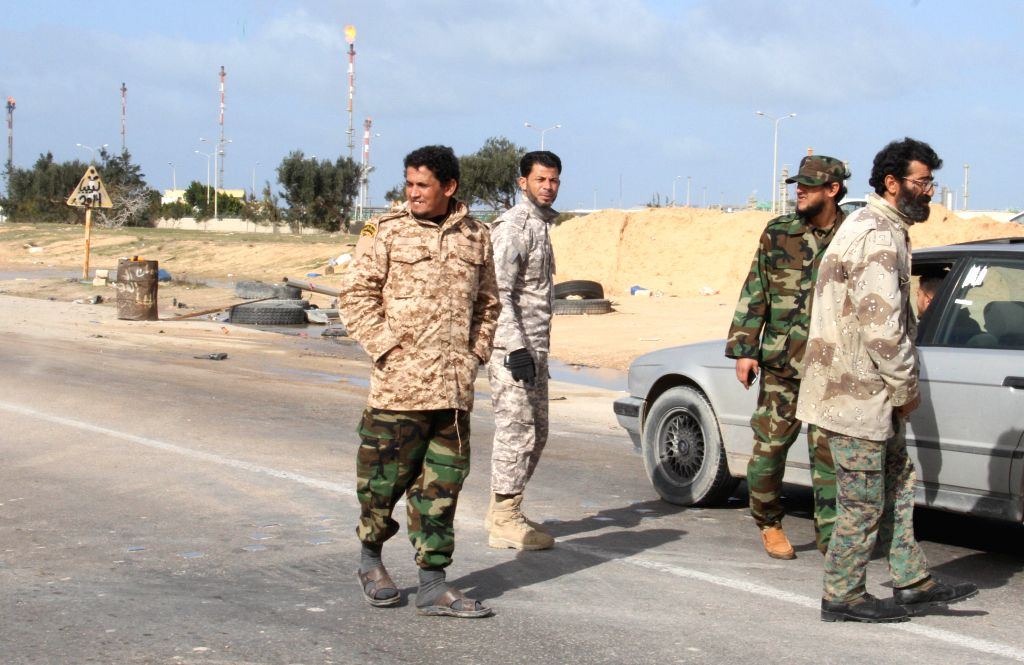 Some Libya Dawn fighters stand at a check point on the outskirts of Zuwara in western Libya, Jan. 6, 2015. Clashes continued between Libya Dawn fighters and ...