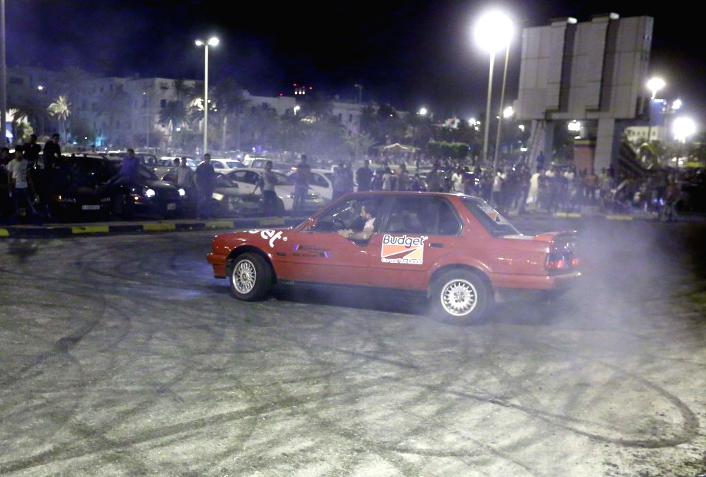 Libyans watch a young man drifting his car in a street in Tripoli July 11, 2014. After breaking the fast during the Islamic holy month of Ramadan, Libyan people ...