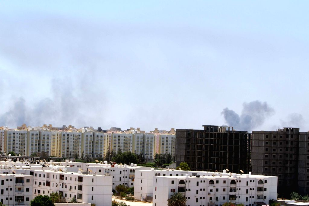 Smoke rises from the streets as heavy fighting goes on between rival militia groups on July 23, 2014, in Tripoli, Libya. Deadly clashes erupted between Islamist ...