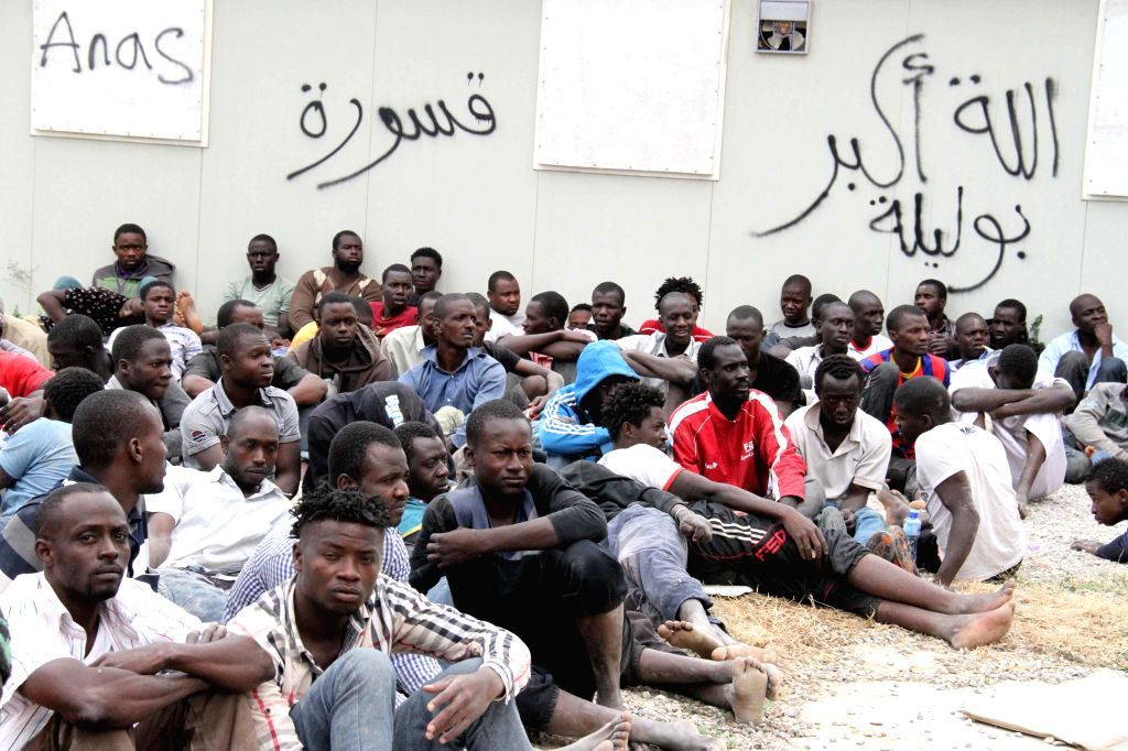 TRIPOLI, June 4, 2015 (Xinhua) -- Illegal immigrants wait in a detention center in central Tripoli, Libya, on June 4, 2015. Libyan security forces on Thursday arrested 441 Africans planning to illegally immigrate to Europe, according to security sour
