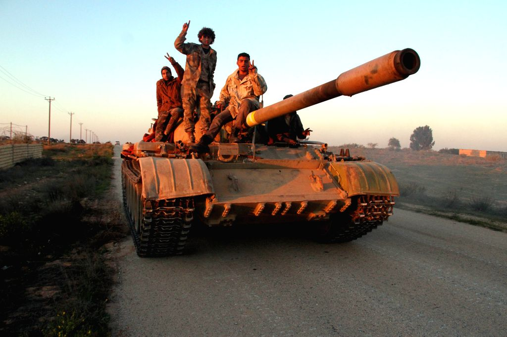 Some Libya Dawn fighters pose for pictures on their tank near Libya's capital city of Tripoli, on March 11, 2015. Clashes erupted on Wednesday between Libya Dawn ...