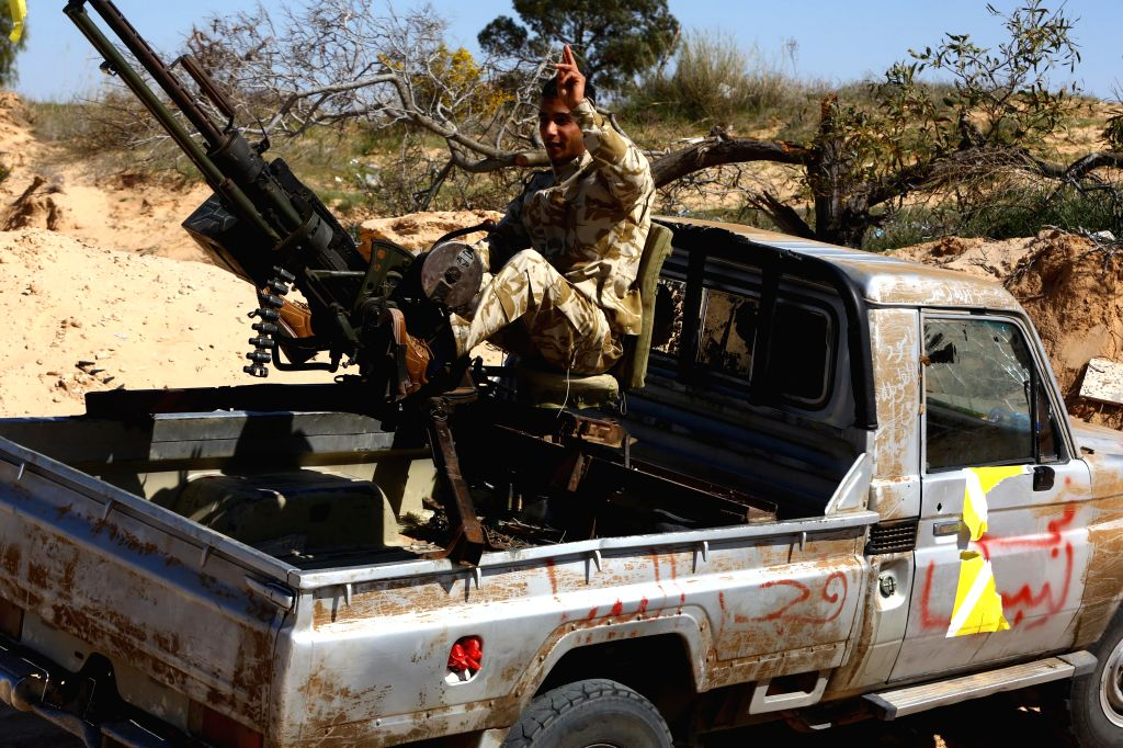 TRIPOLI, March 12 A Libya Dawn fighter poses for photo on an armored vehicle after a fierce battle near Libya's capital city of Tripoli, on March 12, 2015. Clashes erupted on Thursday ...