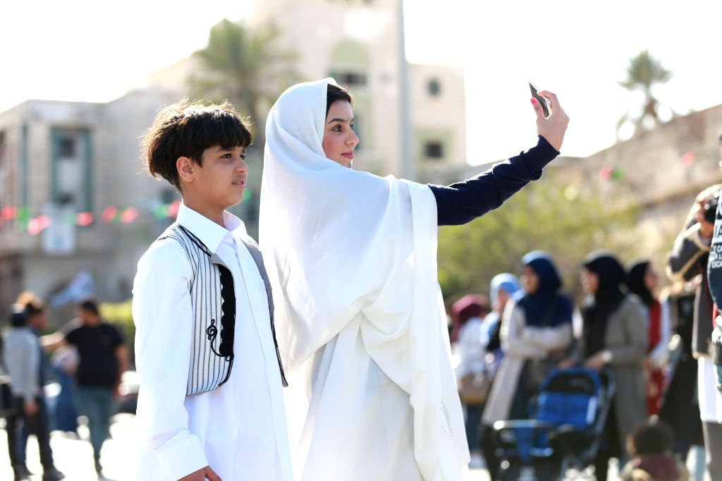 """TRIPOLI, March 13, 2017 - A Libyan woman wearing traditional costumes takes a selfie with her son during an event to mark the """"National Day of Traditional Dress"""" at Martyrs' Square in ..."""