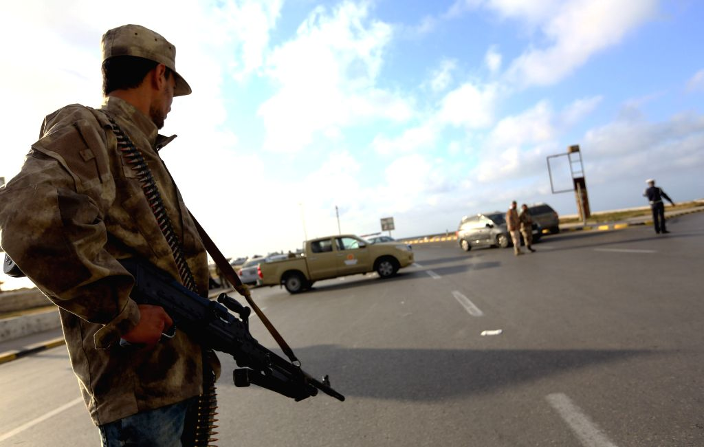 TRIPOLI, March 15, 2017 - A member of forces loyal to Libya's Government of National Accord (GNA) guards a checkpoint in the Hay al-Andalus neighbourhood in Tripoli, Libya, March 14, 2017 following ...