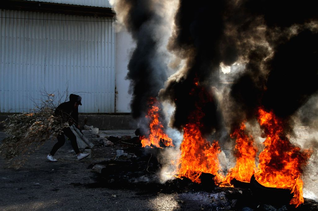TRIPOLI, Nov. 12, 2019 - Protesters burn tyres to block the road in the northern city of Tripoli, Lebanon, on Nov. 12, 2019. Lebanese President Michel Aoun on Tuesday called on the protesters to ...