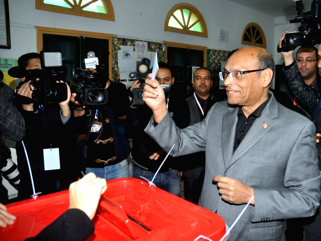 Tunisian presidential candidate, incumbent President Moncef Marzouki casts his vote at a polling station in Tunis, capital of Tunisia, Dec. 21, 2014. Polling started ..