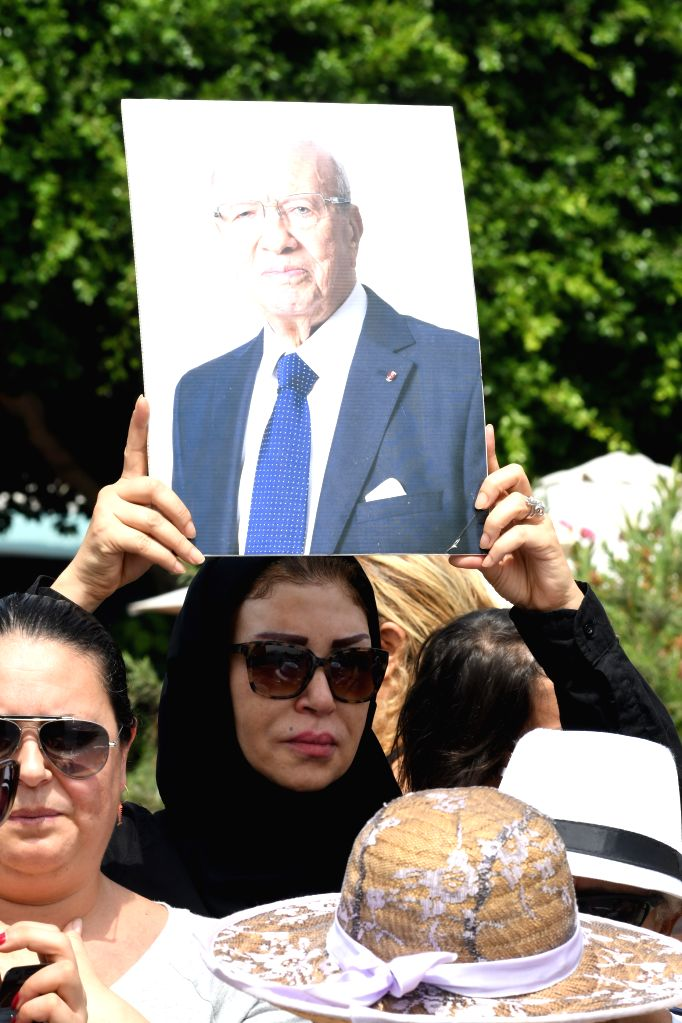 TUNIS, July 27, 2019 - A woman holds a portrait of late Tunisian President Beji Caid Essebsi during his state funeral in Tunis, Tunisia, July 27, 2019. Tunisian people paid on Saturday their last ...