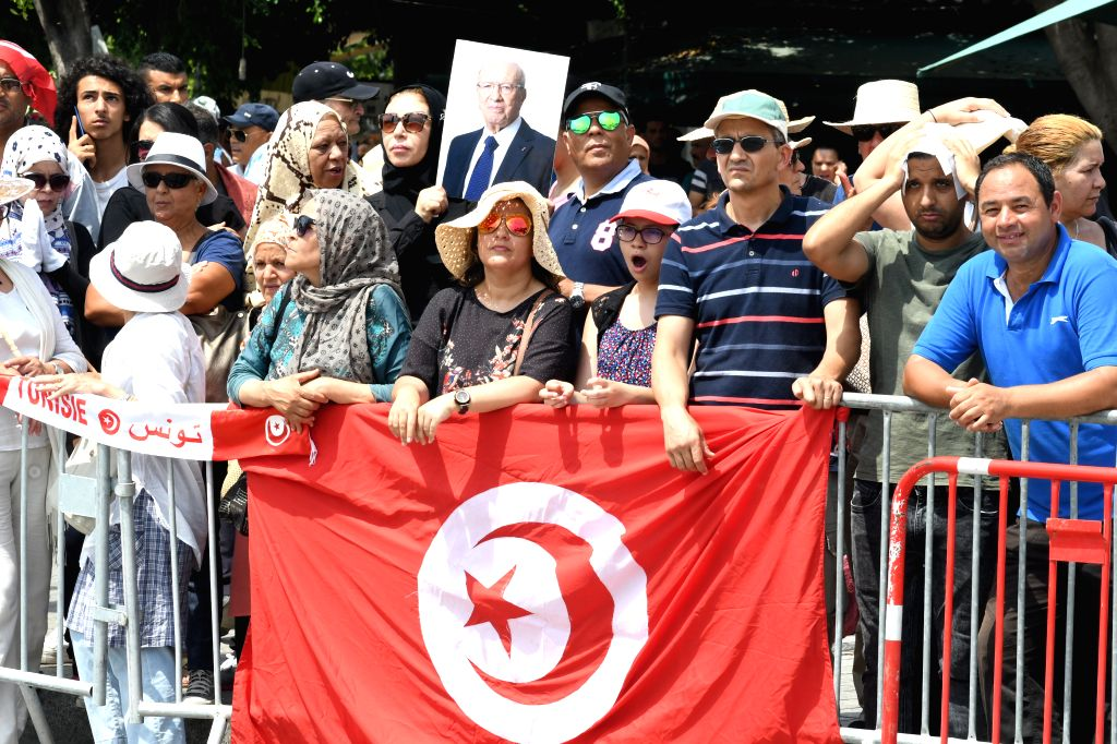 TUNIS, July 27, 2019 - People watch the military procession accompanying the coffin of late Tunisian President Beji Caid Essebsi during his state funeral in Tunis, Tunisia, July 27, 2019. Tunisian ...