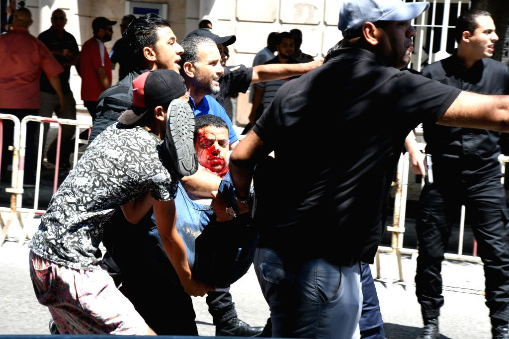 TUNIS, June 27, 2019 (Xinhua) -- People carry an injured policeman to an ambulance from the site of a bomb attack in Tunis, Tunisia, June 27, 2019. Two members of Tunisian security forces were injured Thursday in a suicide bomb attack on a police veh