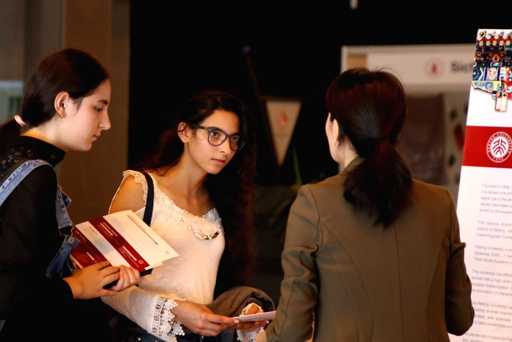 "TUNIS, Sept. 3, 2019 - Tunisian students consult a representative from Peking University on studying information at the exhibition of ""China Campus 2019"" in Tunis, Tunisia, on Sept. 3, ..."