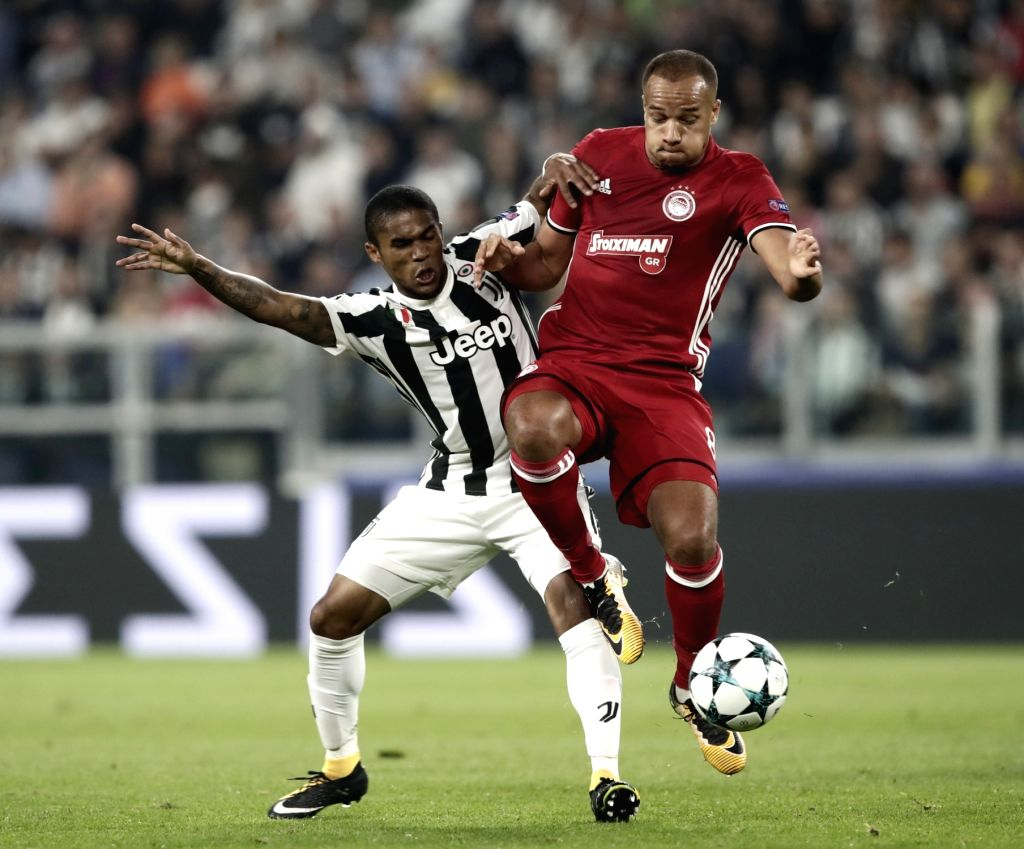 TURIN, Sept. 28, 2017 - Juventus' Douglas Costa (L) vies with Olimpiacos' Vadis Odjidja during the UEFA Champions League group D match between Juventus and Olimpiacos in Turin, Italy, Sept. 27, 2017. ...