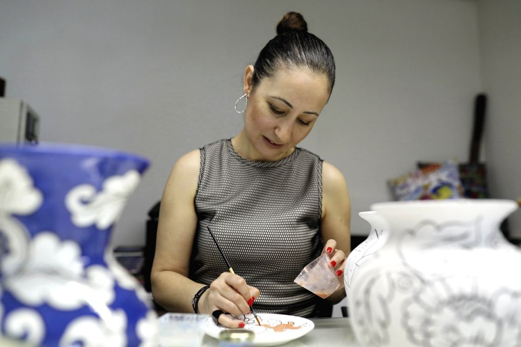 Turkish tile and ceramic artist Ozlem Varol paints on a tray in a studio in Istanbul, Turkey, on June 24, 2020. Ozlem Varol has been offering a new way of doing ... - Ozlem Varol