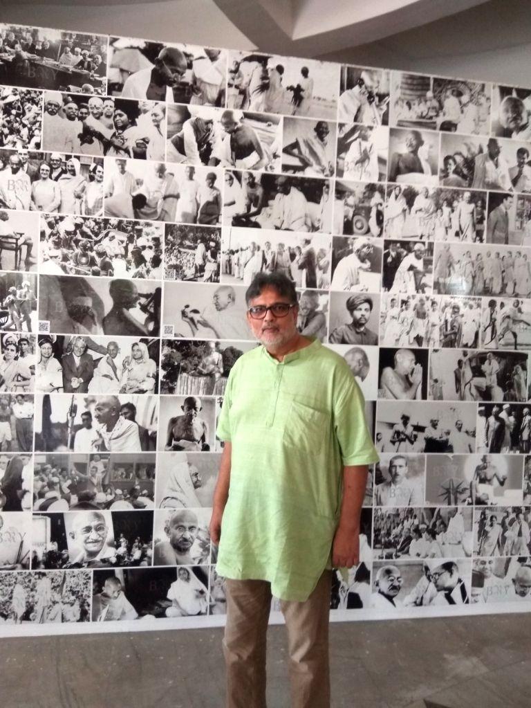 Tushar Gandhi looks the collage of Mahatma Gandhi's photographs at Bapu Ghat. - Tushar Gandhi
