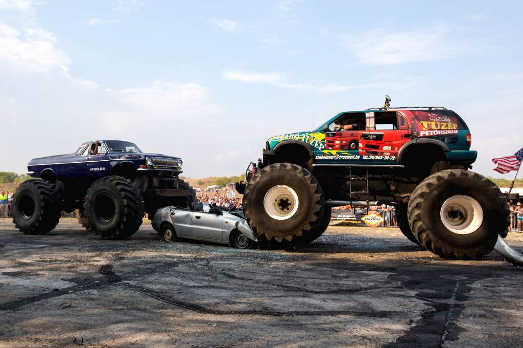 Two Bigfoots smash a car at a show during the 14th U.S. Car Festival in Komarom, Hungary, on Aug. 15, 2015.