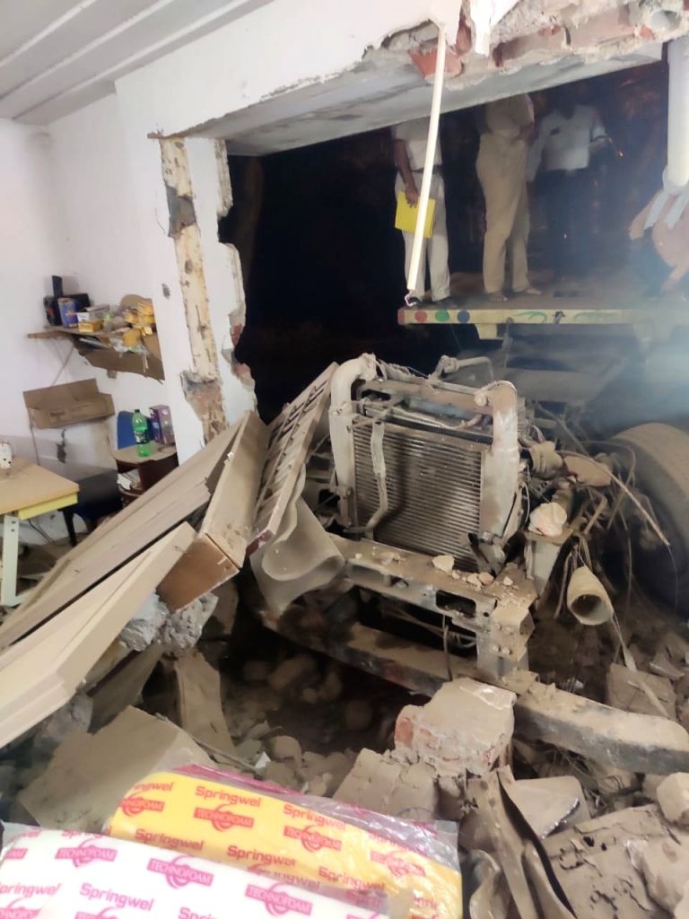 Two die after a truck rams into a factory .