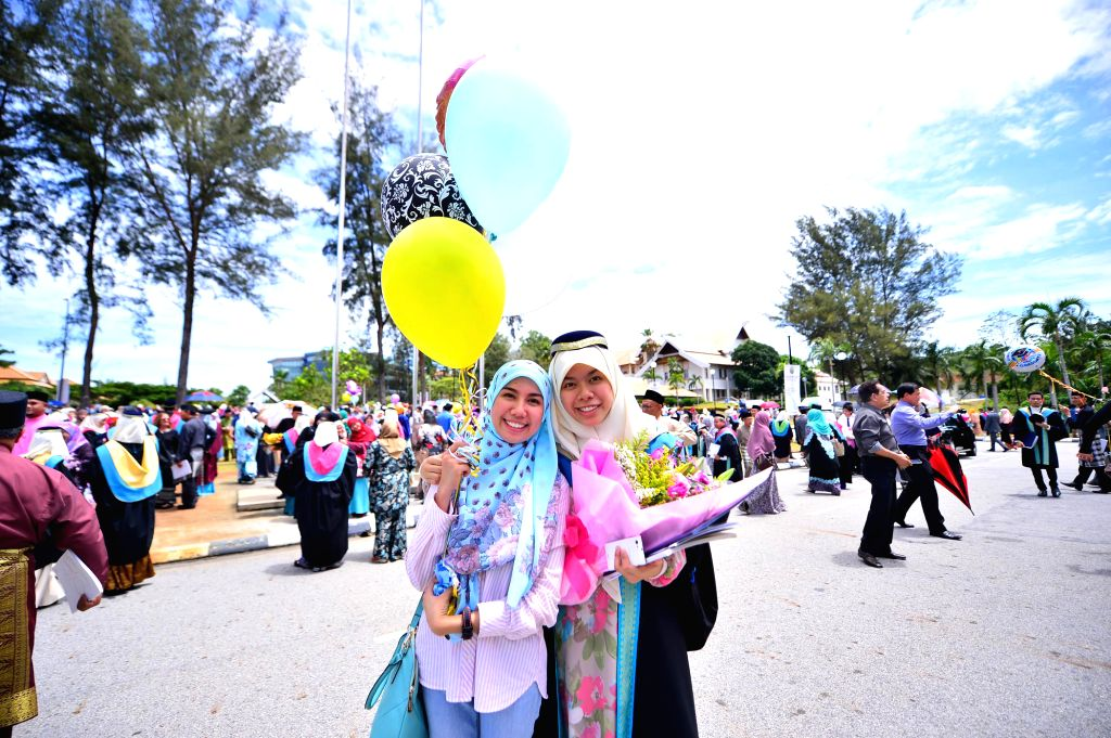 Two graduates of the University Brunei Darussalam (UBD) pose for photos after their convocation in Bandar Seri Begawan, capital of Brunei, on Oct. 15, ...