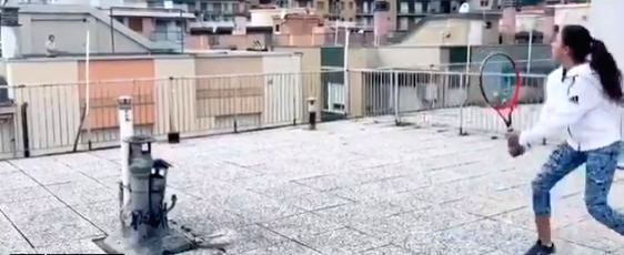 Two Italy women play rooftop tennis maintaining social distance.