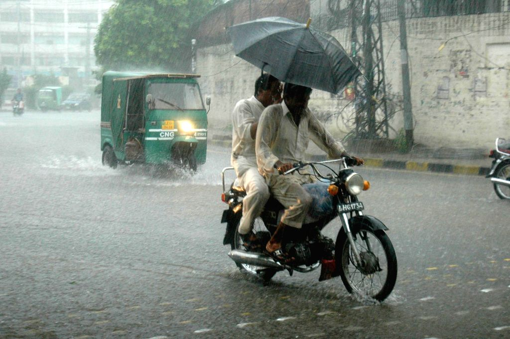 Two men ride a motorbike in heavy rain in eastern Pakistan's Lahore, July 24, 2015. An estimated 285,000 people have been affected by floods in Chitral District, ...