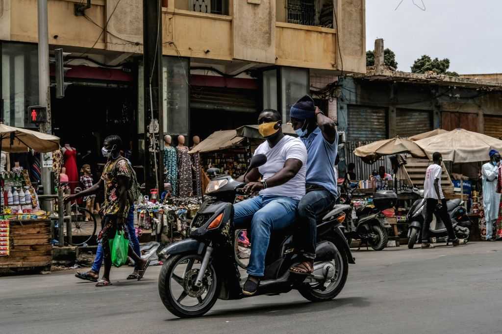 Two men wearing face masks ride a motorbike in Dakar, Senegal, on July 1, 2020. Four months after the outbreak of the COVID-19 pandemic on March 2 in Senegal, the ...