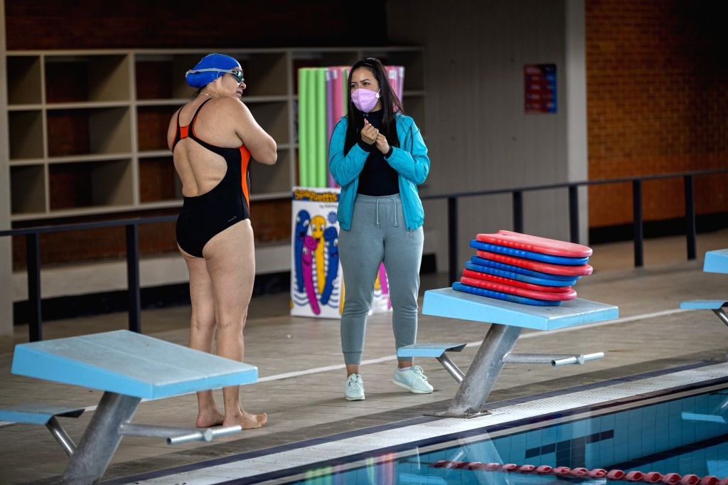Two women talk in a natatorium in Mexico City, Mexico, Aug. 10, 2020. Some natatoriums in Mexico City have reopened to the public with epidemic prevention ...