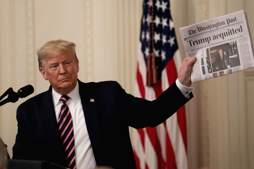 U.S. President Donald Trump holds up a copy of The Washington Post at the White House in Washington D.C., the United States, on Feb. 6, 2020. Donald Trump took a ...