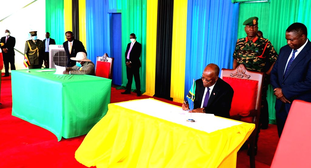 Ugandan President Yoweri Museveni ( L, front) and Tanzanian President John Magufuli (R, front) sign an agreement in Chato, Tanzania, on Sept. 13, 2020. Tanzanian ...