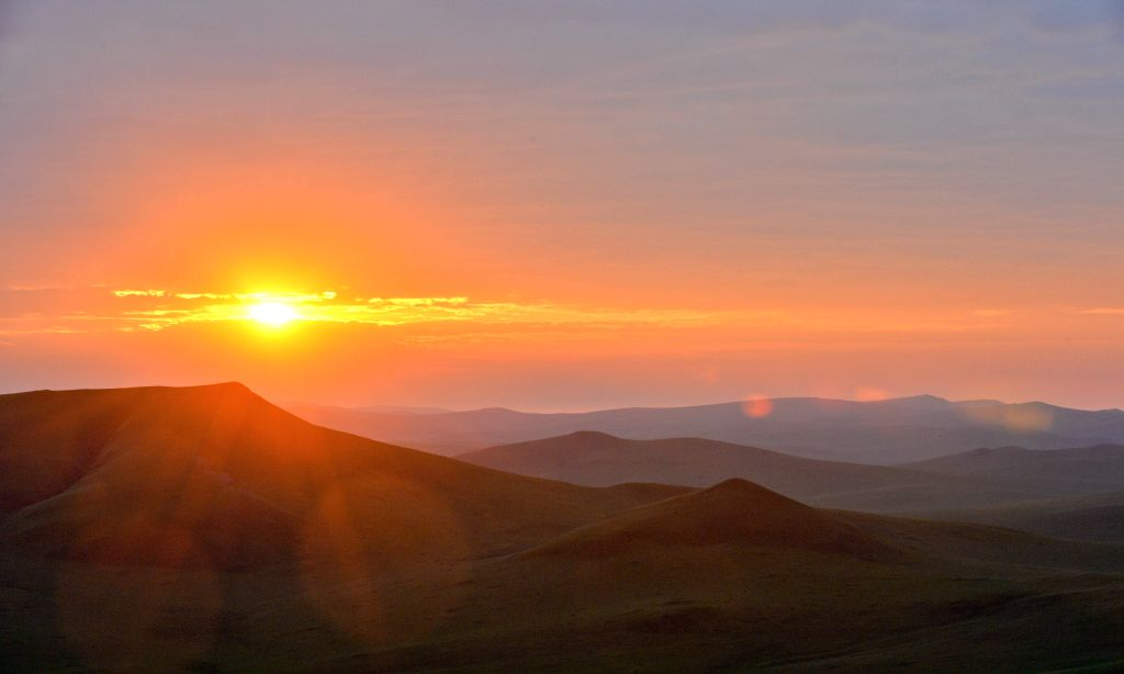 Photo taken on June 22, 2014 shows the sunrise on the Ulgai Grassland in north China's Inner Mongolia Autonomous Region. The Ulgai Grassland boasts a rich flora and ..