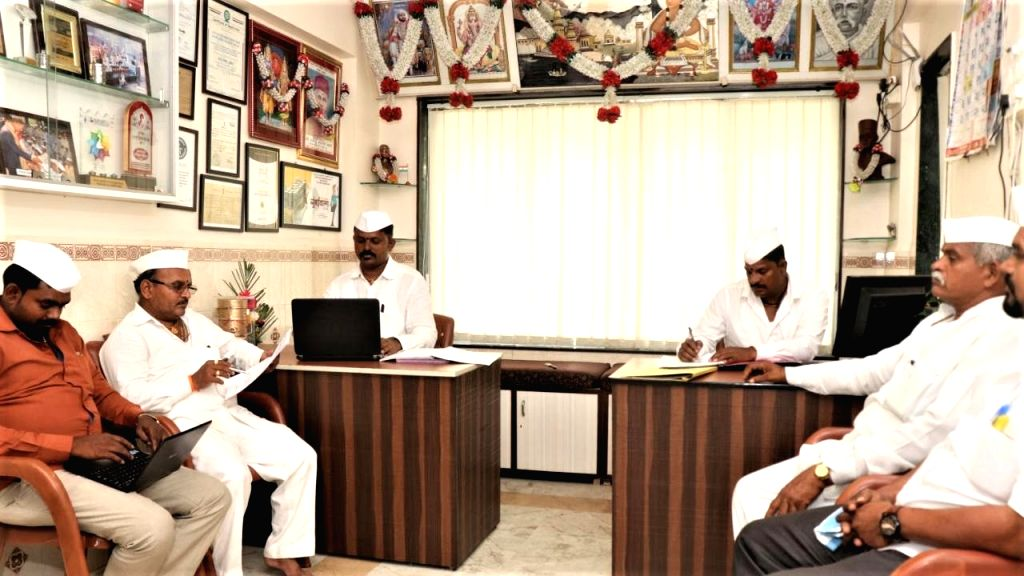 Ulhas S. Muke and Ramdas B. Karvande in Dabbawalas office with lords and laurels on the walls.