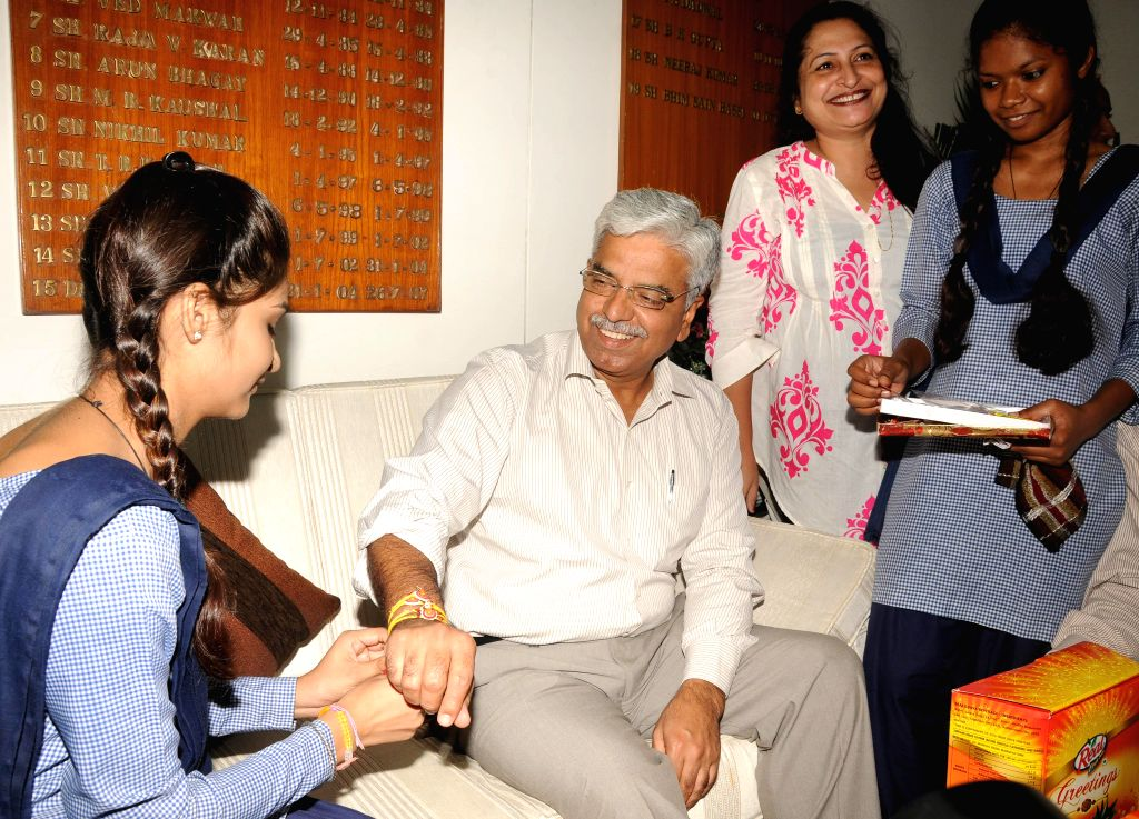 Underprivileged  children tie Rakhis on the wrist of Delhi Police Commissioner B S Bassi in New Delhi on Aug 7, 2014.